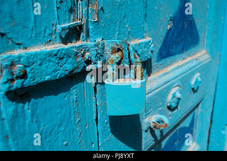 Close up of padlock and latch on a blue painted wooden door - Stock Photo