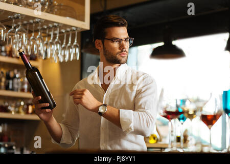 Handsome nice man holding a bottle of wine - Stock Photo