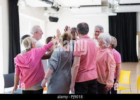 Active seniors high-fiving in circle huddle - Stock Photo