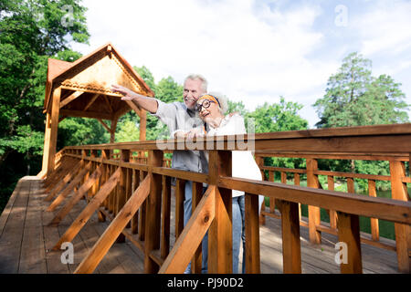 Couple of retired man and woman having rest standing on big wooden bridge - Stock Photo