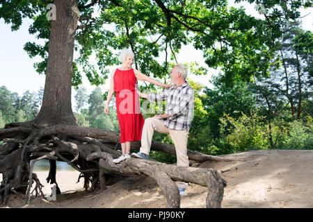 Beaming happy retired wife and husband spending leisure time in nature - Stock Photo