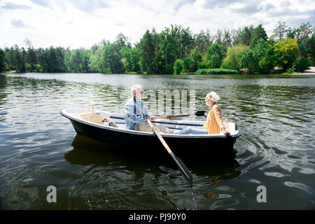 Aged couple having nice boat ride while having very romantic date - Stock Photo
