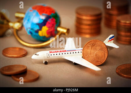 Miniature airplane with label Cheap airman and cent coins, Miniaturflugzeug mit Aufschrift Billigflieger und Centmünzen - Stock Photo