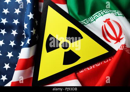 Flags of the USA and Iran and radioactivity warning, Iranian nuclear agreement, Fahnen von USA und Iran und Radioaktivität-Warnschild, iranisches Atom - Stock Photo