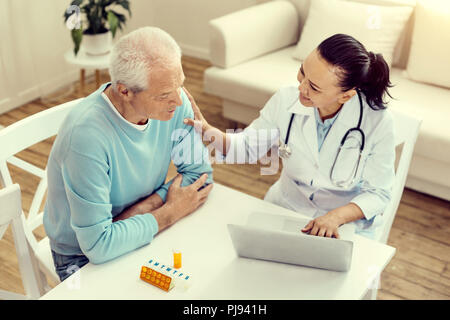Mindful nurse cheering retired patient and smiling - Stock Photo