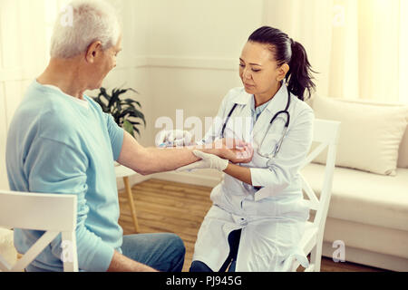 Female nurse vaccinating retired gentleman - Stock Photo