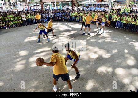 SAN FERNANDO CITY, Philippines (July 10, 2018) U.S. Navy sailors play basketball with local students at La Union High School as a part of Maritime Training Activity (MTA) Sama Sama 2018. The week-long engagement focuses on the full spectrum of naval capabilities and is designed to strengthen the close partnership between both navies while cooperatively ensuring maritime security, stability and prosperity. - Stock Photo