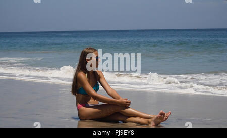 Girl in the sun glasses sits on a sandy beach among the waves and looks at the sea.Young girl relaxing at Tropical Beach. Recreation and pampering on the seashore ocean, river, lake in summer and sunny day. - Stock Photo