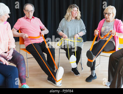 Active seniors exercising in circle, using straps to stretch legs - Stock Photo