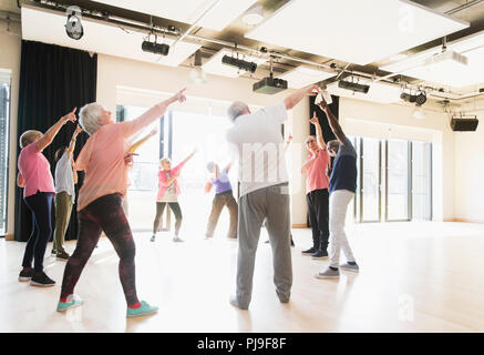 Active seniors dancing, exercising and stretching in circle - Stock Photo