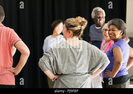 Smiling active seniors exercising in circle - Stock Photo