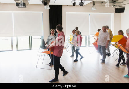Active seniors carrying chairs in community center - Stock Photo