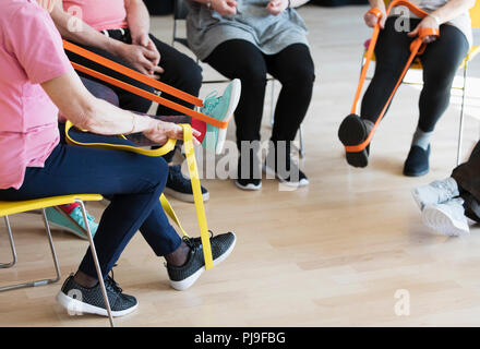 Active seniors stretching, exercising with straps - Stock Photo