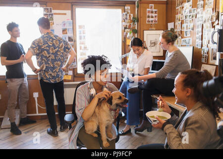 Creative business people with dog working and eating in office - Stock Photo