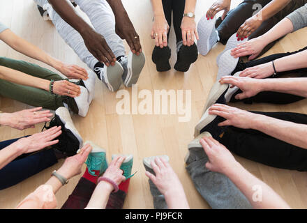 Active seniors stretching legs in circle - Stock Photo