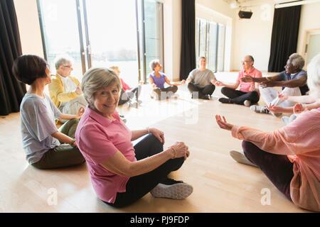 Portrait smiling active senior woman meditating in circle - Stock Photo