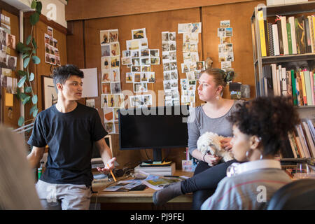 Creative designers with dog brainstorming in office - Stock Photo