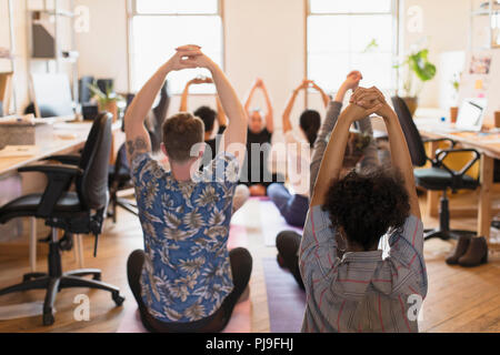 Creative business people practicing yoga in office - Stock Photo