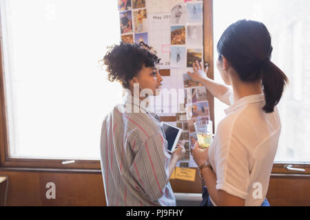 Creative female designers reviewing photographs - Stock Photo