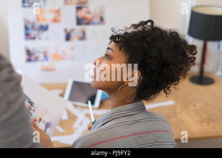 Attentive creative female designer reviewing proofs in office - Stock Photo