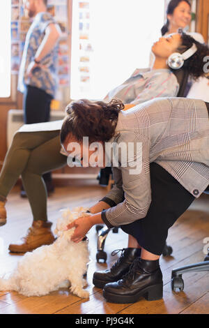 Creative businesswoman petting cute dog in office - Stock Photo