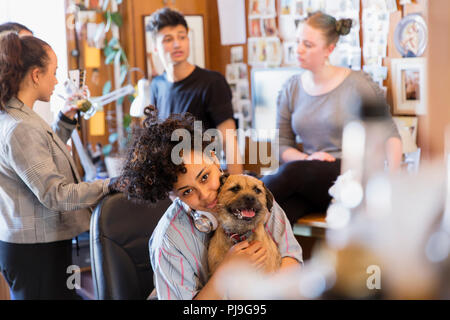 Portrait creative female designer with dog in office - Stock Photo