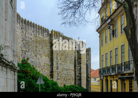 Street with typical building in the Alfama district, and the Cathedral wall, in Lisbon, Portugal - Stock Photo