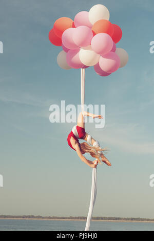 Girl does acrobatic stunts. She floats in the air on balloons. - Stock Photo