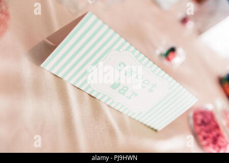 Sweet Bar Paper Sign on Wedding Table with Coloured Sweets - Stock Photo