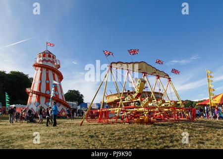 Bristol, UK: August 09, 2018: Families enjoy the traditional helter skelter slide and amusement park rides at Bristol's International Balloon Feista.