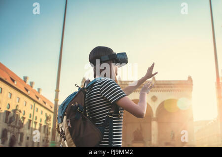 Girl tourist in glasses virtual reality. Virtual trip to Germany. The concept of virtual tourism. In the background is the square on Leopoldstrasse in Munich. - Stock Photo