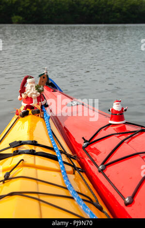 Santa Claus ornaments decorate kayaks in the water at Christmas on Sanibel Island, Florida. - Stock Photo
