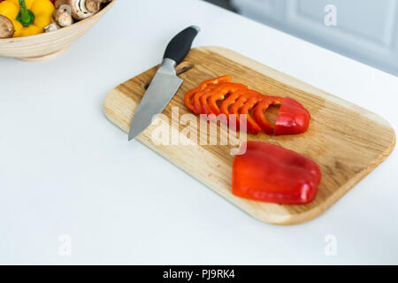 high angle view of sliced bell pepper and knife on wooden cutting board - Stock Photo