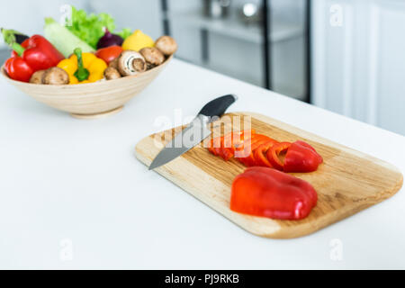 close-up view of sliced bell pepper and knife on wooden cutting board - Stock Photo