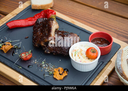 Delicious juicy BBQ pork ribs served with Coleslaw salad on cutting board - Stock Photo