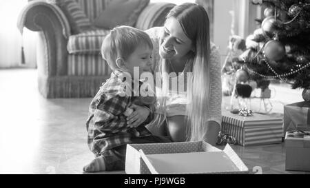 Black and white portrait of cheerful little boy hugging plush toy he received for CHristmas Stock Photo