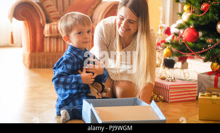 Adorable little boy sitting under Christmas tree and hugging plush toy he received in gift box from Santa Stock Photo