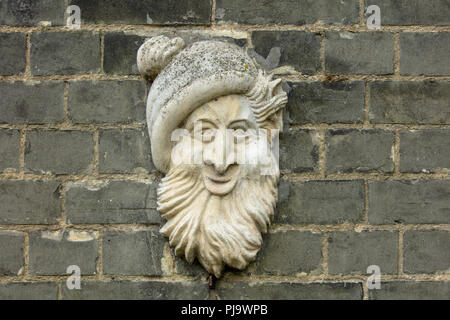 Creative use of a wall sculpture: stone hand carved casual face of a man fixed to a dark weathered outdoor brick wall in Norwich, England, UK. - Stock Photo
