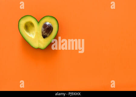 Heart-shaped slices of avocado on orange background - Stock Photo