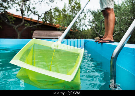 closeup of a young caucasian man cleaning the water of a swimming pool, with a leaf skimmer mounted in a telescopic pole - Stock Photo