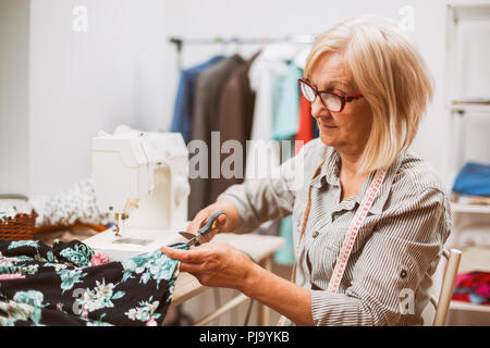 Adult woman is sewing in her studio. - Stock Photo