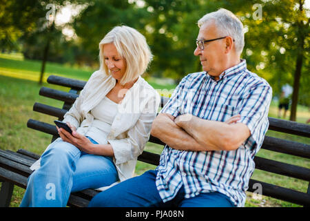 Senior man is angry while his woman is messaging on phone. - Stock Photo
