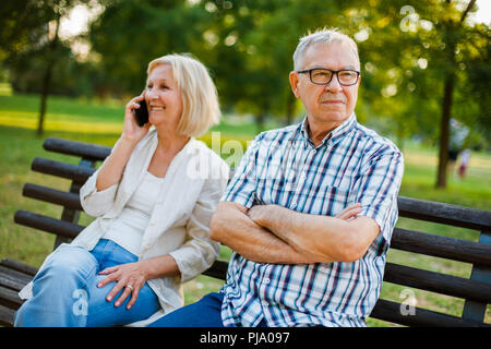 Senior man is angry while his woman is talking on phone. - Stock Photo