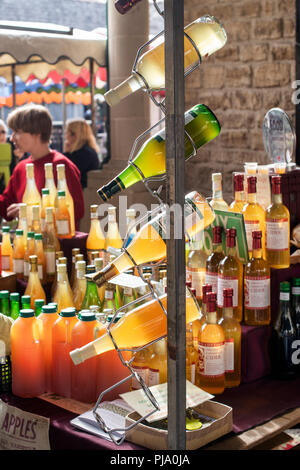 Local cider for sale on a stall at Stroud farmers market. Stroud, Gloucestershire, England - Stock Photo