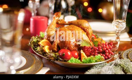 Closeup photo of hot freshly baked turkey on festive table against Christmas tree - Stock Photo