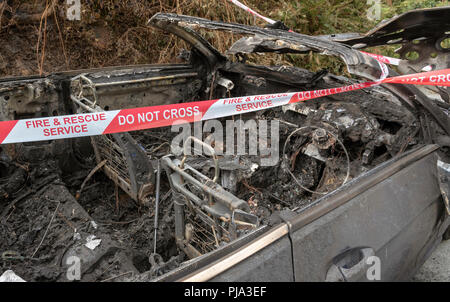 Fire damaged car showing the Fire & Rescue Service Do Not Cross plastic ribbon. - Stock Photo