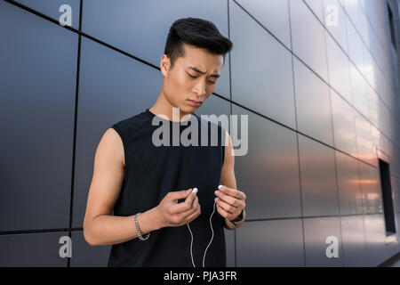 serious young asian sportsman putting on earphones at city street - Stock Photo