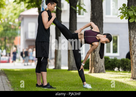 asian sportsman helping female athlete to stretch on grass in park - Stock Photo