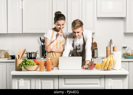young couple using laptop during cooking in kitchen