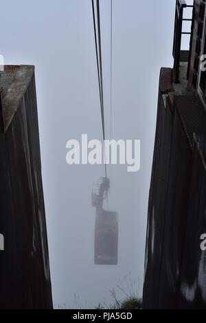 The upper section (el Cable) of the teleferique or cable car from Fuente De. The car is looming out of the mist as it comes in to dock. - Stock Photo